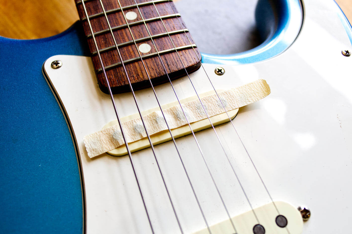 Fender strat with tape on Neck pickup to remove metal filings